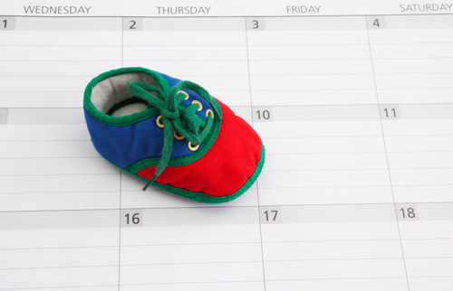 Colorful Baby bootie on a claendar background. Could be used for concepts such as due date, baby announcement, baby shower invitation, pregnancy announcement or planning to have a baby.