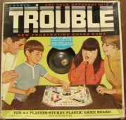 Trouble is a game similar to Headache. You pop the dice in the bubble at the centre of the board and pieces are moved in accordance to the number. If you landed on an opponent's piece you sent their piece back to the start.