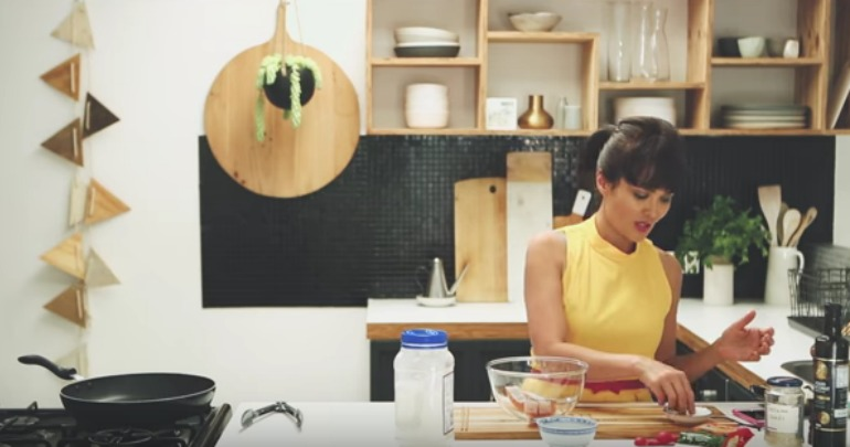 Yumi whips up a dish in the kitchen.