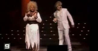 A still from a Channel 9 video of one of Wickety Wak impersonating Dolly Parton and Kenny Rogers.