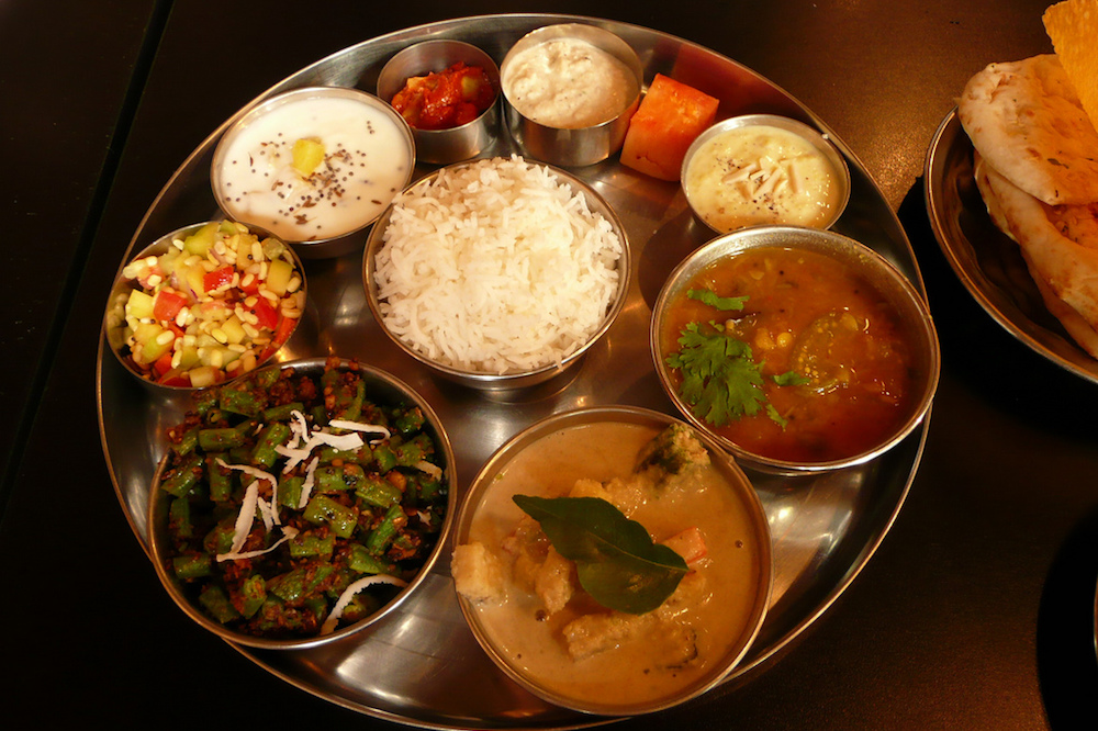 A traditional thali with rice, several different dishes and dessert