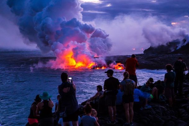 Tourists watch as the lava spills into the sea in the Volcanos National Park