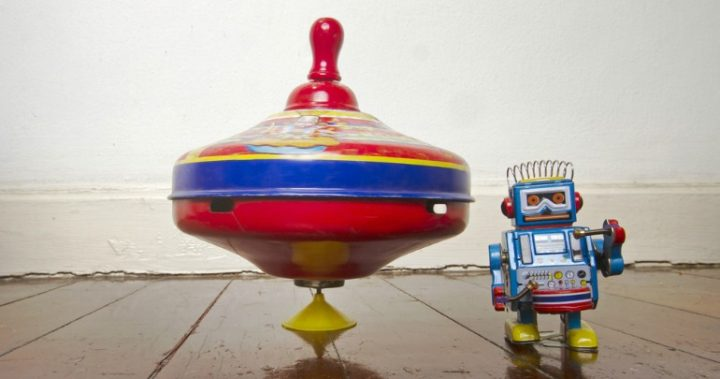 Vintage spinning top and robot on wooden floor.