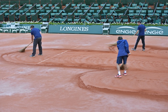 Sweepers work on the court at Roland Garros. Source: Getty