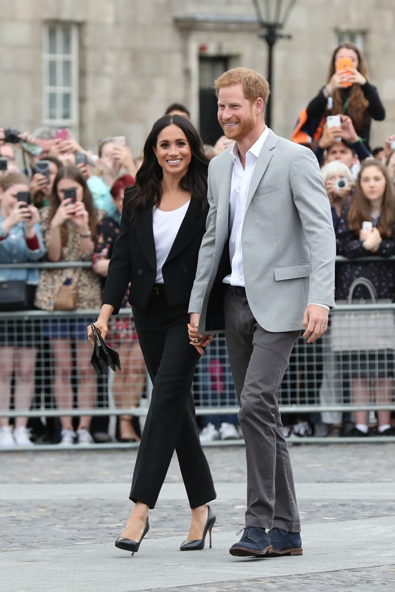Meghan cut a stylish figure in a Givenchy pantsuit, meanwhile Prince Harry looked dapper in a grey suit. Source: Getty