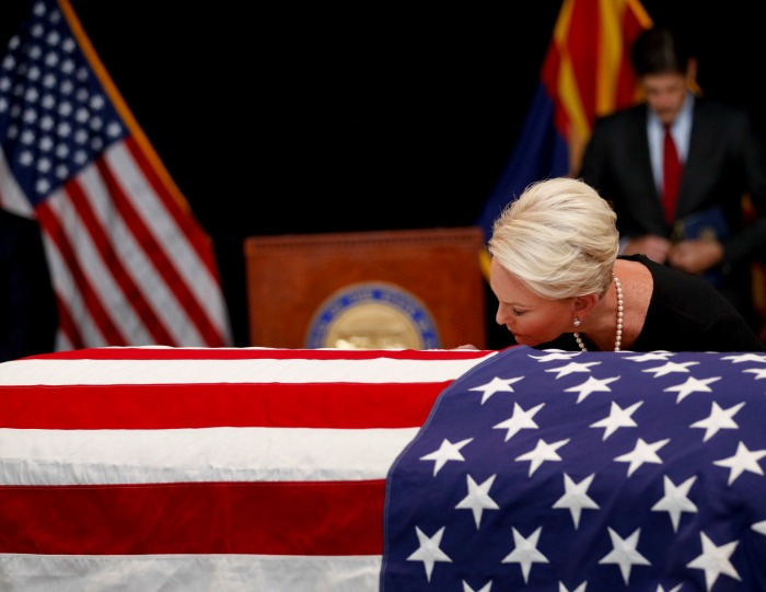 Cindy McCain tenderly touched her cheek to the flag drape. Source: Getty.