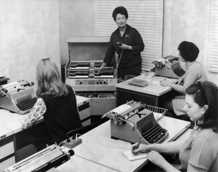 A woman uses Phillips stenolab equipment to train a group of students in taking dictation. Source: Getty