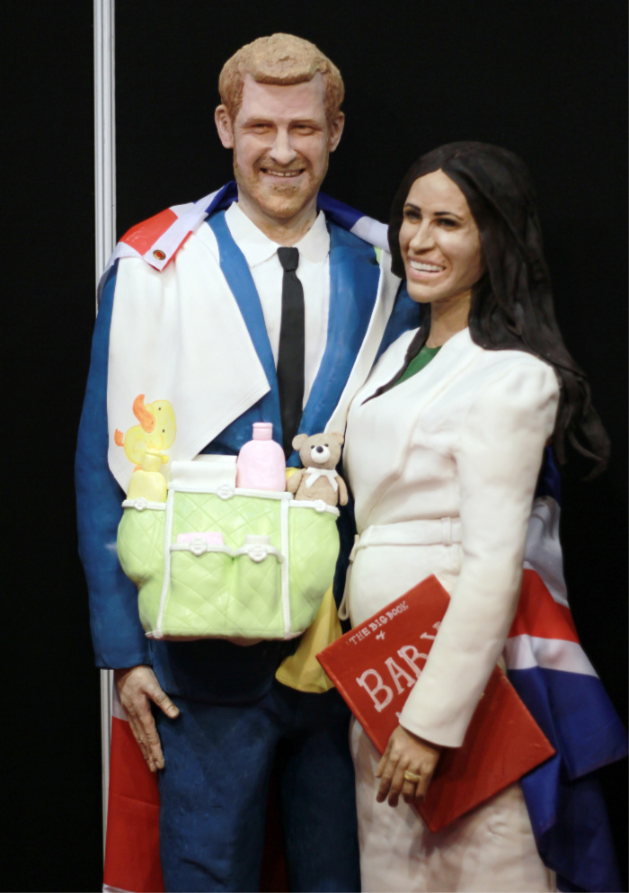 A baker in England created a cake depicting Prince Harry and Meghan carrying baby essentials.