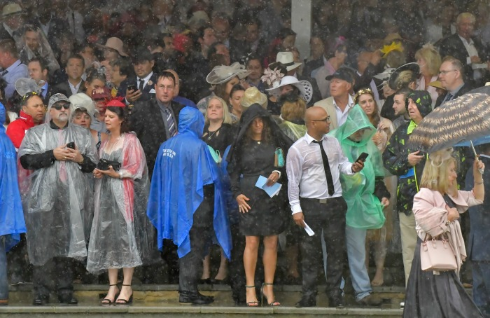 Crowds rushed to take cover under umbrellas and ponchos to watch the races from outside. Source: Getty.